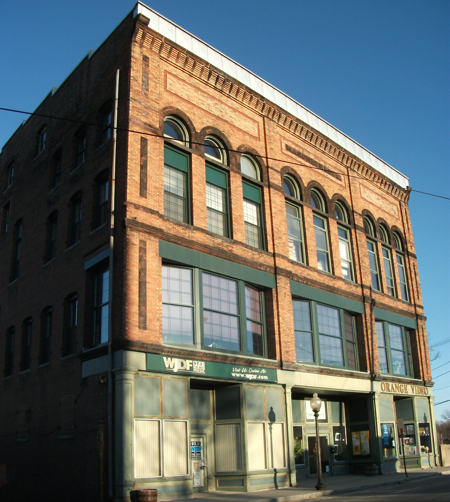 Quabbin Mediation Building in Downtown Orange, with the sun shinning on the façade.