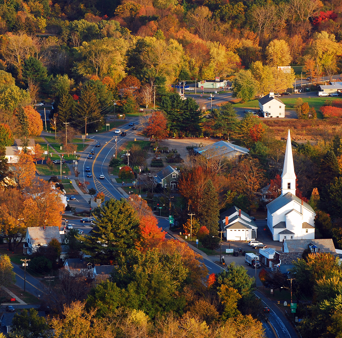 An aerial shot of a valley city with fall leaves and cars buzzing around everywhere.